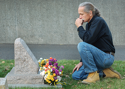 man mourning at a grave